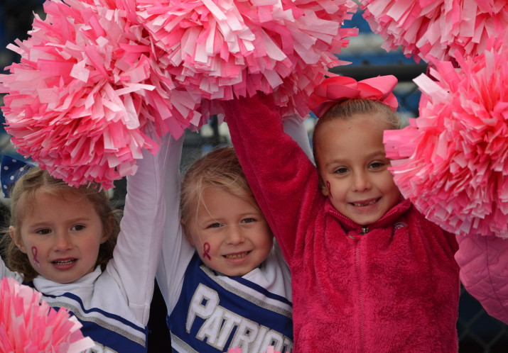 Our Flag cheerleaders sporting pink pom poms in honor of Cancer Awareness Month