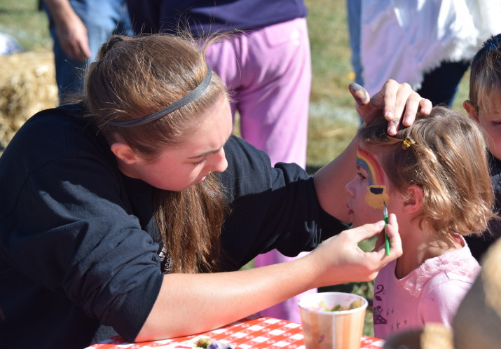A student volunteer from Caring Hands painting faces at the Fall Festival