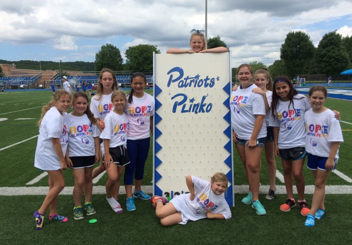 Girls from our Competition Cheer team manning their Plinko game at Relay for Life